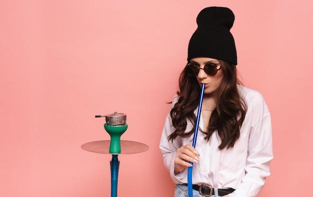 Eine junge frau raucht eine wasserpfeife