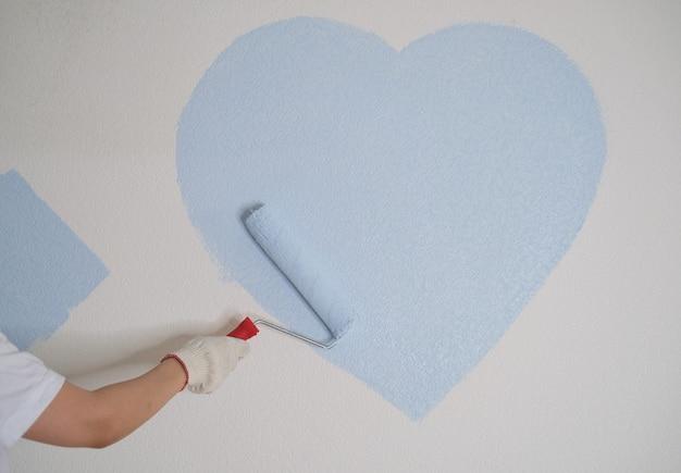 Eine junge frau repariert die wohnung und streicht die wände blau.