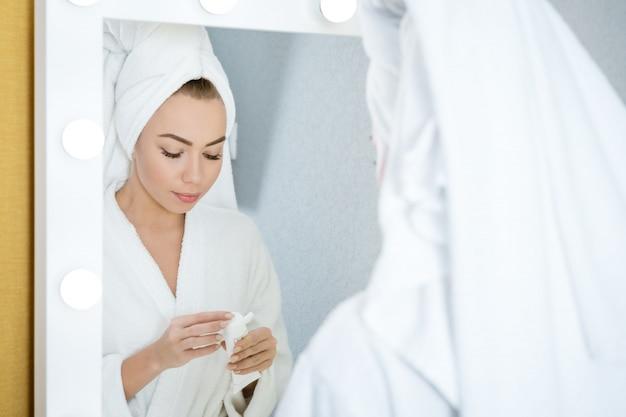 Eine junge frau schaut mit einem handtuch auf dem kopf in den spiegel und hält eine gesichtscreme. hautpflegekonzept bei hom