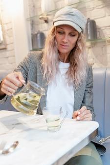 Eine junge frau schenkt sich in einem café tee ein. moderne hübsche blondine in einer mütze. gesundheitsvorsorge. vertikal.