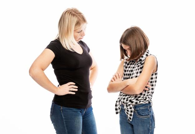 Eine junge frau schimpft mit der tochter eines teenagers. der konflikt der generationen. weiße wand.