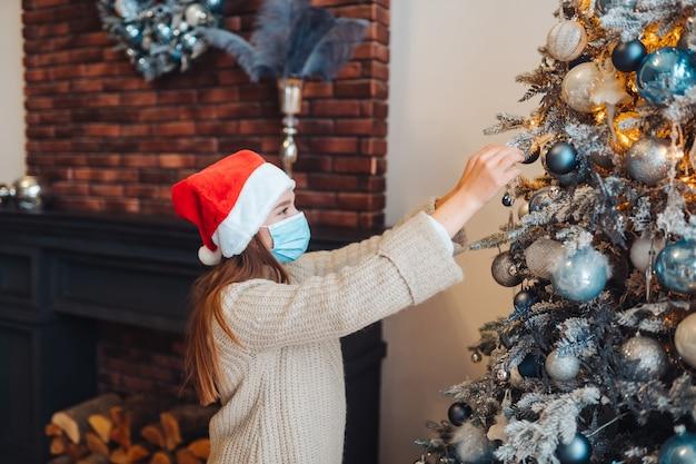 Eine junge frau schmückt den weihnachtsbaum mit einer medizinischen maske