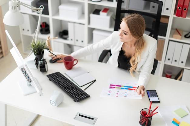 Eine junge frau sitzt am computertisch im büro, hält einen bleistift in der hand und arbeitet mit dokumenten.