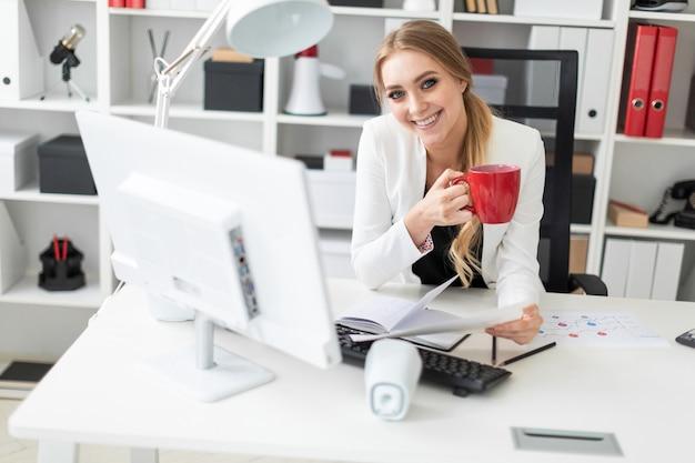 Eine junge frau sitzt am computertisch im büro und hält eine tasse und dokumente. vor der frau auf dem tisch liegen diagramme.