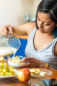 Eine junge frau sitzt am tisch und gießt milch auf einen teller mit müsli und haferflocken