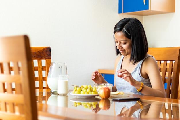 Eine junge frau sitzt am tisch und isst müsli, haferflocken und obst