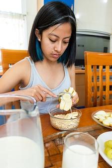 Eine junge frau sitzt am tisch und serviert banane auf einem teller mit müsli und haferflocken