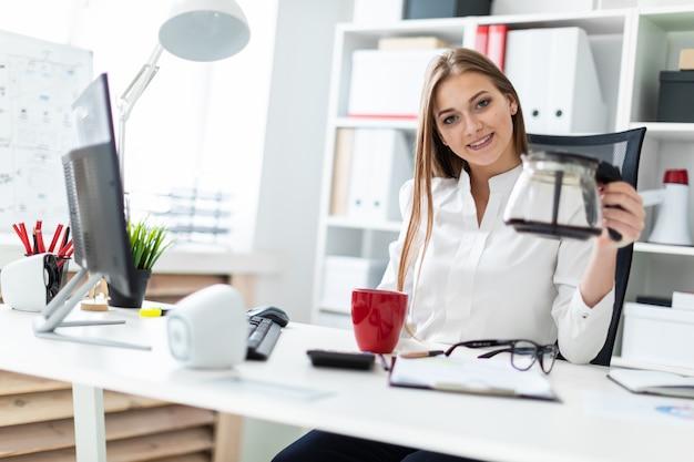 Eine junge frau sitzt an einem computertisch im büro und gießt seinen kaffee ein.