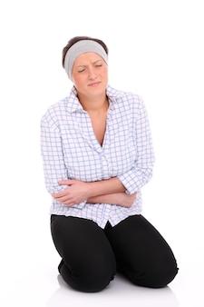 Eine junge frau sitzt auf dem boden und leidet an bauchschmerzen