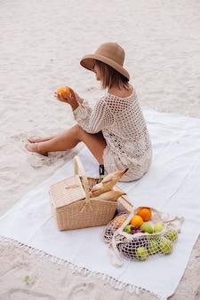 Eine junge frau sitzt auf dem handtuch in einem strohhut und einer weißen strickkleidung mit picknickkorb