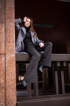 Eine junge frau sitzt hoch am geländer und schaut nach unten. frau des modellauftritts posiert