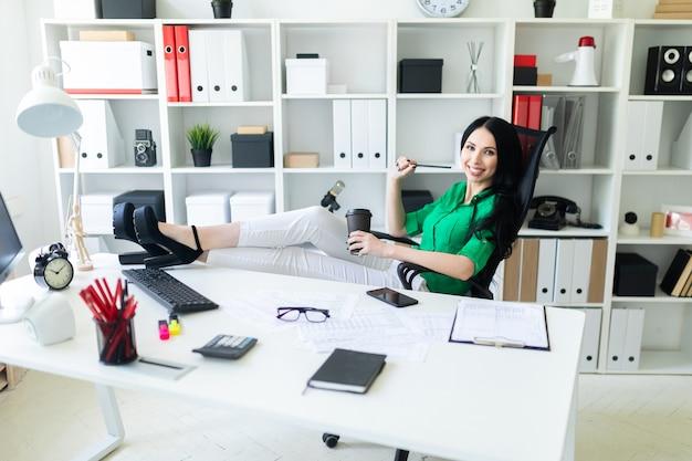 Eine junge frau sitzt im büro, wirft die beine auf den tisch und hält ein glas kaffee in der hand.