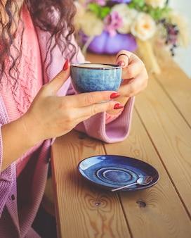 Eine junge frau sitzt in einem café und hält eine tasse kaffee in den händen.