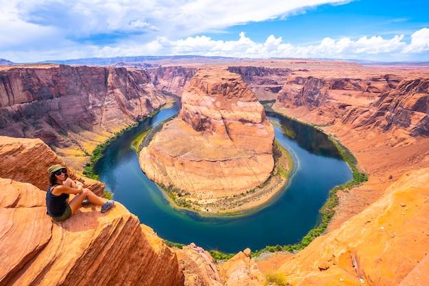 Eine junge frau sitzt und betrachtet horseshoe bend und den colorado river im hintergrund, arizona. uns