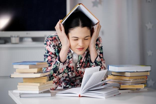 Eine junge frau sitzt vor einem stapel papiere und einem computer, der ihren kopf hält