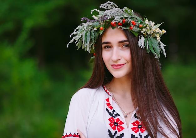 Eine junge frau slawischen aussehens mit einem kranz aus wilden blumen auf der midsummer.