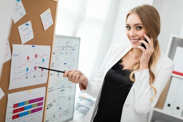 Eine junge frau steht in der nähe des brettes mit aufklebern, spricht am telefon und hält einen bleistift in der hand.