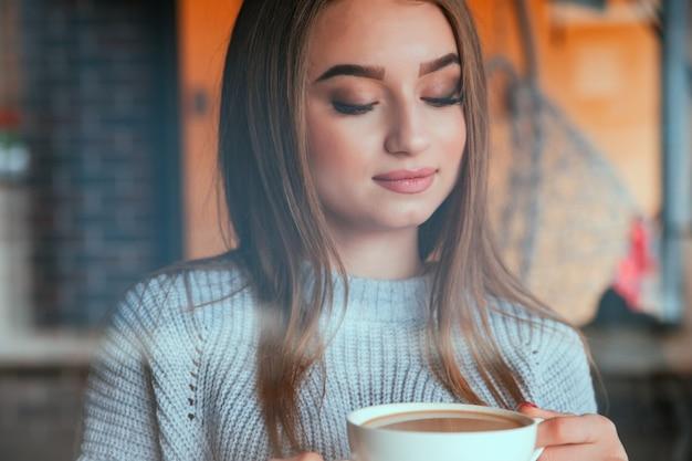 Eine junge frau steht mit einer tasse kaffee am fenster.