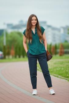 Eine junge frau trägt stilvolle freizeitkleidung und genießt ihren spaziergang im park