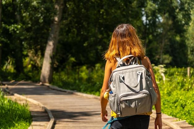 Eine junge frau trekking auf dem fußweg entlang einer fußgängerbrücke zwischen la garette und coulon, marais poitevin das grüne venedig, in der nähe der stadt niort, frankreich