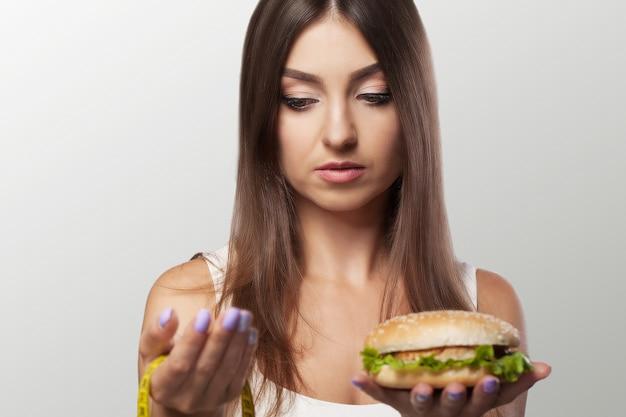Eine junge frau trifft die wahl zwischen gesundem und schädlichem essen. sport. diät. das konzept von gesundheit und schönheit.