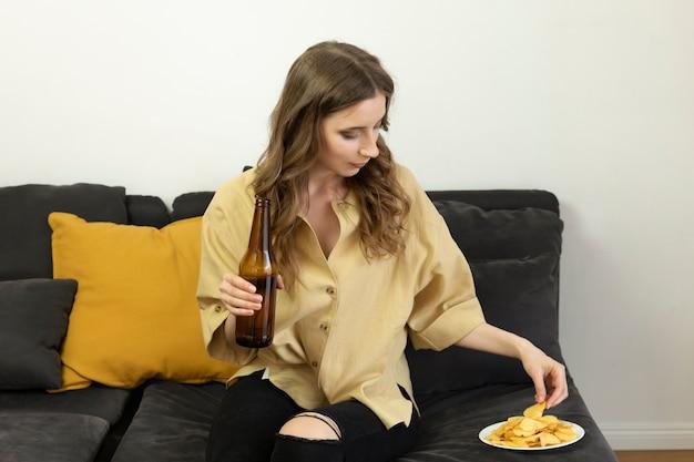 Eine junge frau trinkt bier und isst pommes