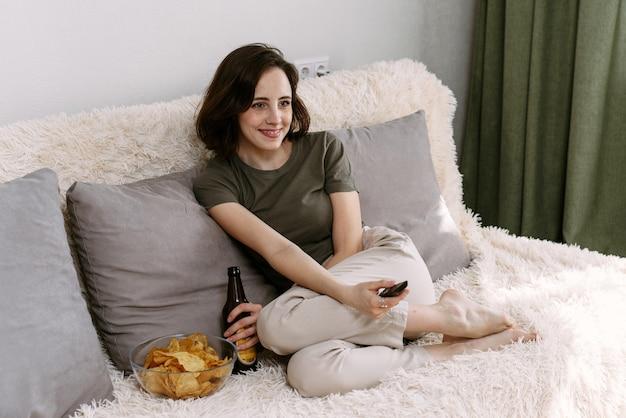 Eine junge frau trinkt bier und isst zu hause pommes. entspannen sie sich zu hause beim fernsehen und filmen.