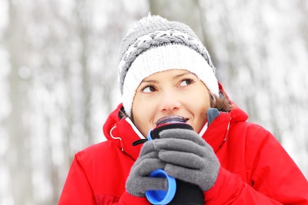 Eine junge frau trinkt heißes getränk in einem winterwald