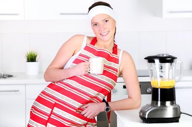 Eine junge frau trinkt kaffee in der küche
