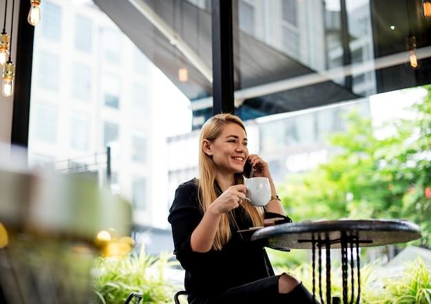 Eine junge frau trinkt kaffee und telefoniert