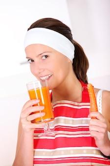 Eine junge frau trinkt karottensaft in der küche