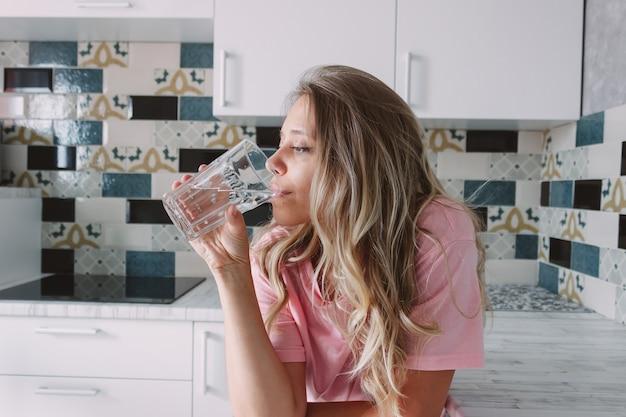 Eine junge frau trinkt wasser aus einem großen transparenten glas, das in der küche steht