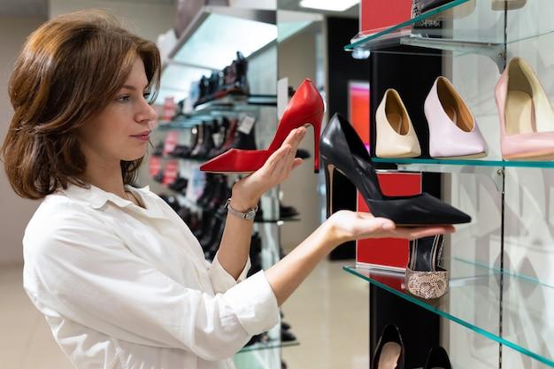 Eine junge frau überlegte, ob sie zwischen roten und schwarzen bootsschuhen in high heels wählen sollte.