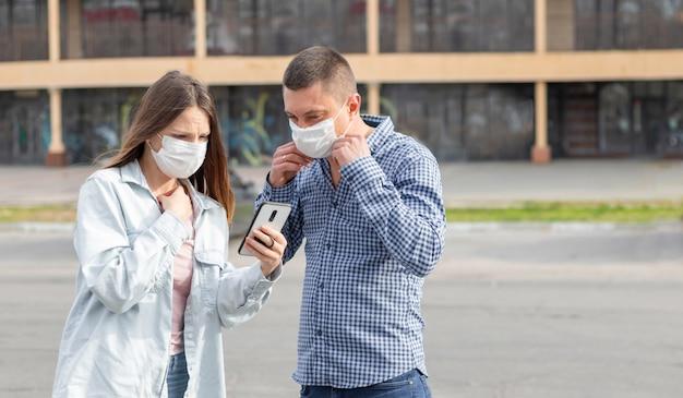 Eine junge frau und ein mann mit medizinischen operationsmasken in der stadt lasen schlechte nachrichten am telefon.