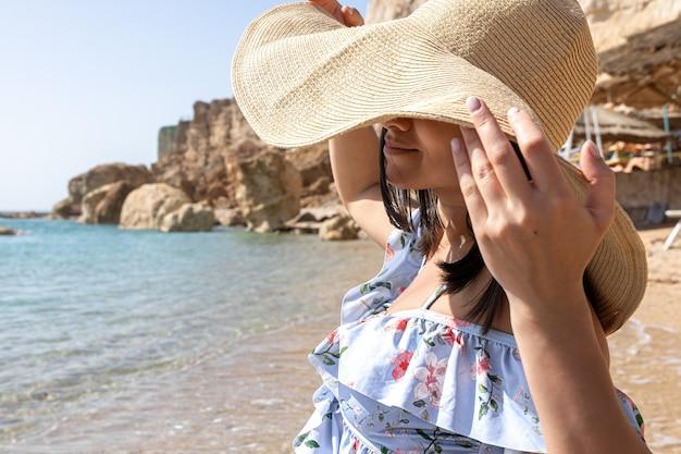 Eine junge frau versteckt ihr gesicht vor der sonne unter einem großen hut an der küste.