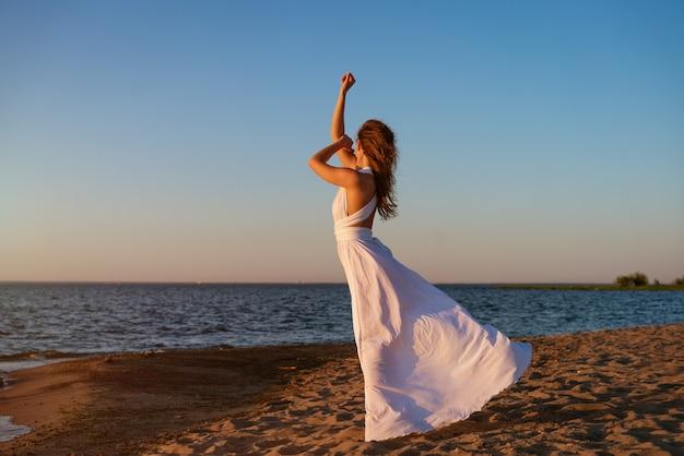 Eine junge frau von europäischem aussehen im sommer in einem weißen kleid am meer steht bei sonnenuntergang...