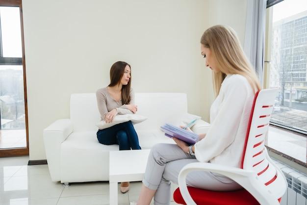 Eine junge frau während einer depression kommuniziert mit einem psychologen im büro