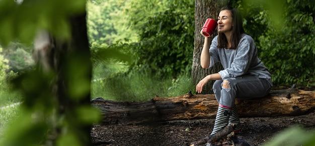 Eine junge frau wärmt sich in der nähe eines erloschenen feuers mit einer tasse wärmenden getränks im wald zwischen den bäumen auf