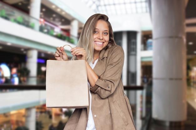 Eine junge frau zeigt eine öko-papiertüte mit kopienraum für das logo auf einem verschwommenen hintergrund des einkaufszentrums