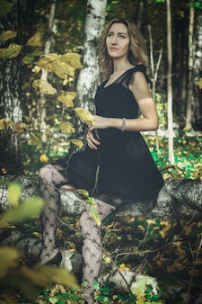 Eine junge freundliche hexe in einem schwarzen kleid