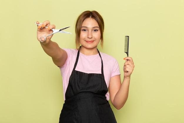 Eine junge friseurin der vorderansicht im rosa t-shirt und im schwarzen umhang, die bürste und schere halten, die auf grün lächeln