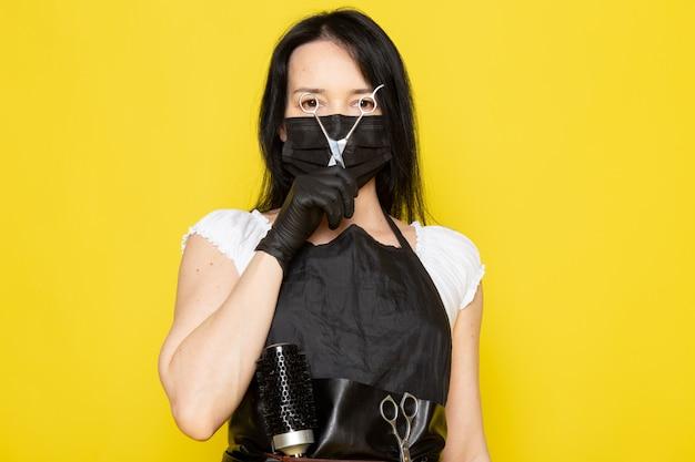 Eine junge friseurin der vorderansicht im schwarzen umhang des weißen t-shirts, das schere in schwarzen handschuhen der schwarzen sterilen maske hält