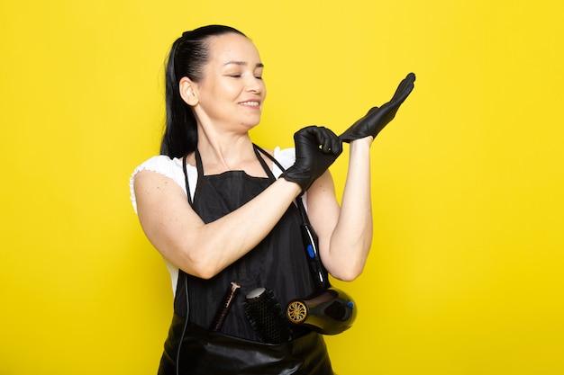 Eine junge friseurin der vorderansicht im schwarzen umhang des weißen t-shirts, der lächelnde schwarze handschuhe trägt