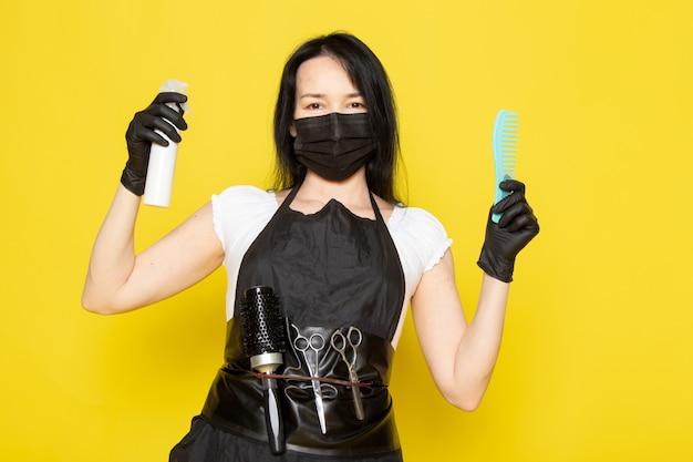 Eine junge friseurin der vorderansicht im schwarzen umhang des weißen t-shirts, der spray und haarbürste in schwarzen handschuhen der schwarzen sterilen maske hält