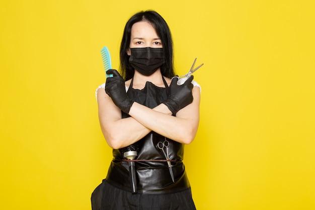 Eine junge friseurin der vorderansicht im schwarzen umhang des weißen t-shirts hält blaue haarbürste und schere in schwarzen handschuhen der schwarzen sterilen maske