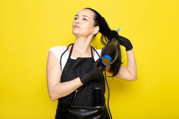 Eine junge friseurin der vorderansicht im schwarzen umhang des weißen t-shirts in den schwarzen handschuhen, die haartrockner und bürste halten, die ihr haar trocknen