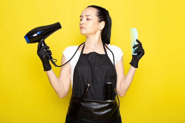 Eine junge friseurin der vorderansicht im schwarzen umhang des weißen t-shirts in den schwarzen handschuhen, die haartrockner und bürste halten