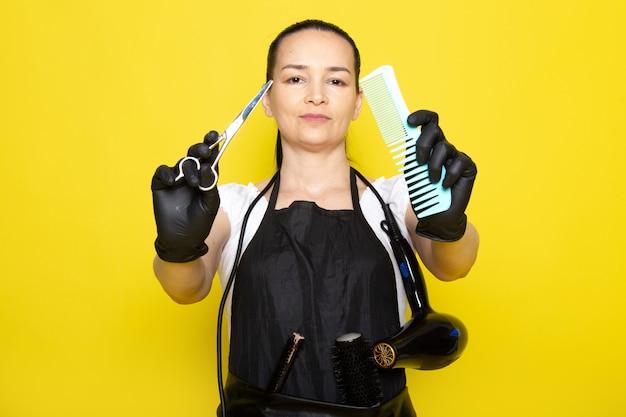 Eine junge friseurin der vorderansicht im schwarzen umhang des weißen t-shirts in den schwarzen handschuhen, die schere und bürste halten