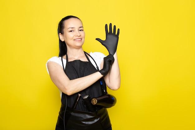 Eine junge friseurin der vorderansicht im schwarzen umhang des weißen t-shirts in den schwarzen handschuhen lächelnd