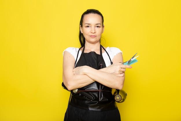 Eine junge friseurin der vorderansicht im schwarzen umhang des weißen t-shirts mit bürsten und fön, die schere halten, die aufwirft